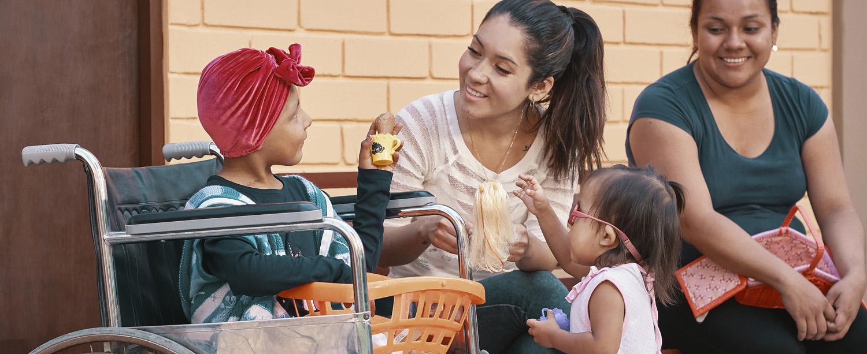 Dos madres con sus hijas, una de ellas sentada en una silla de ruedas. Ambas niñas sostienen juguetes en sus manos.