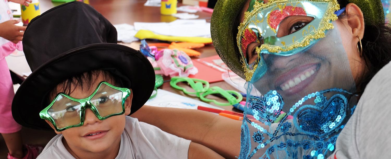 Madre e hijo usando máscaras y gafas decorativas. Detrás se ven los materiales de varias manualidades.