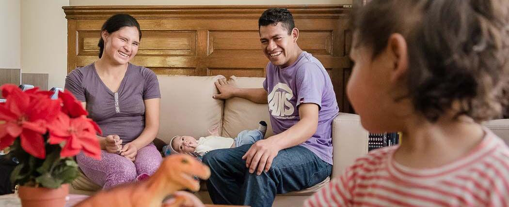 Padre y madre sentados con su bebe en acostado en medio de ellos. Ambos miran a una niñita, frente a ellos, quien los mira también.