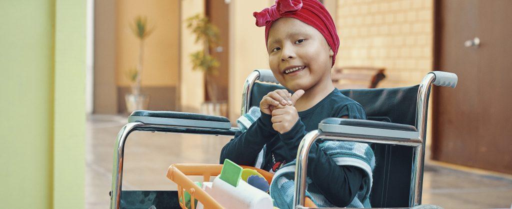 Una pequeña niña sentada en una silla de ruedas sonríe mientras trata de levantar su dedito pulgar.
